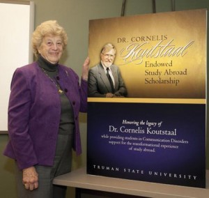 Murilyn Koutstaal poses with a poster celebrating the endowed study abroad scholarship created in honor of her late husband, Cornelis Koutstaal.