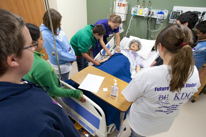A Truman student helps a group of middle school students in the Nursing Lab in the Health Sciences Building.