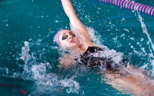 A Truman swimmer performs the backstroke during a meet against Western Illinois.