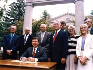 McClain (standing, red tie) was present in 1985 when Gov. John Ashcroft signed House Bill 196, officially changing the University's mission to a statewide public liberal arts and sciences university.